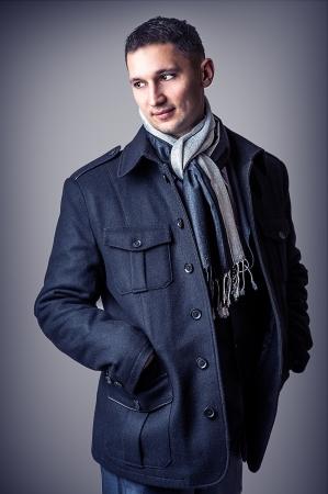 chaqueta de cuero: Hombre joven guapo sexy en abrigo negro y una bufanda ocasional en blanco y negro
