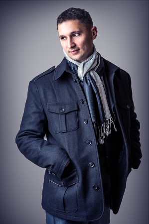 overcoat: Young handsome sexy man in casual black coat and black and white scarf