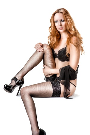Young sexy woman with long curly hair wearing black lingerie; high heel shoes and stockings on white Stock Photo - 16826599
