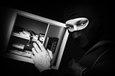 Professional burglar in black ski mask opened a small safe, holding hand gun and aiming Stock Photo - 16992970