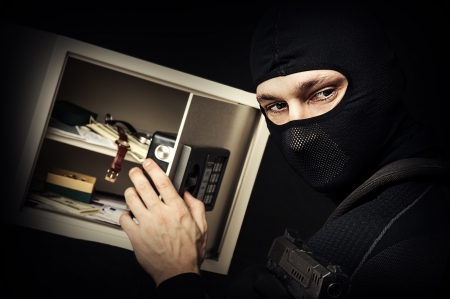 Professional burglar in black ski mask opened a small safe, holding hand gun and aiming photo