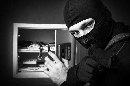 Professional burglar in black mask opened a small safe, holding hand gun and aiming photo