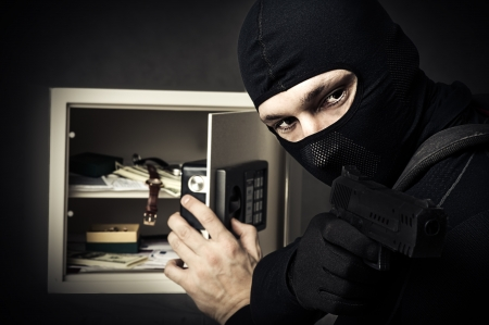 financal: Professional burglar in black mask opened a small safe, holding hand gun and aiming