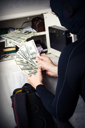 Professional burglar in black ski mask opened a small safe and holding a fan of money Stock Photo - 16992975