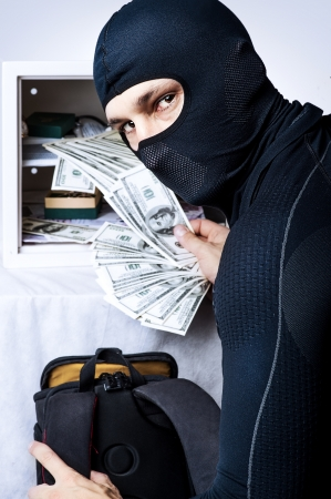 Professional burglar in black mask opened a small safe and holding a fan of money and looking to shot photo