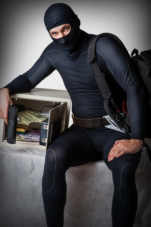financal: Professional burglar in black ski mask opened a small safe, holding hand gun  Stock Photo
