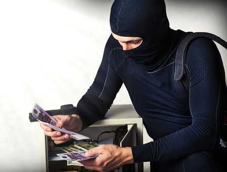 financal: Professional burglar in black ski mask  opened a small safe, holding a lot of money