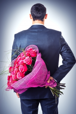 pink flowers: Valentines day. Man hiding behind a bouquet of flowers. Proposal scene  Stock Photo