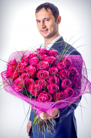 Valentines day. Man holding big bouquet of flowers. Proposal scene  photo