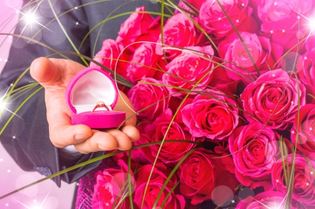 Valentines day. Man with flowers and ring in pink box. Proposal scene  photo