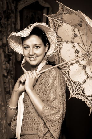 historical periods: Retro portrait of beautiful woman in old hat with a lace umbrella  Stock Photo