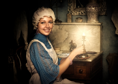 historical periods: Retro portrait of beautiful woman in old cap with candlestick Stock Photo