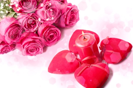 Art Design with beautiful big bouquet of pink roses, candle and red hearts photo