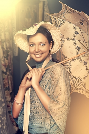 19th century: Retro portrait of beautiful woman in old hat with a lace umbrella  Stock Photo