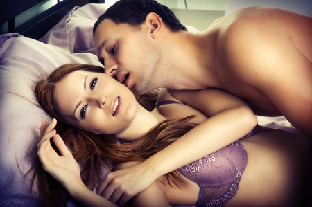 sex couple: Young man kissing woman in darkness bedroom on bed Stock Photo