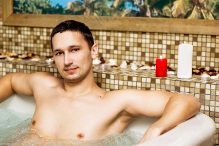 Young man in romantic jacuzzi with flowers and candles photo
