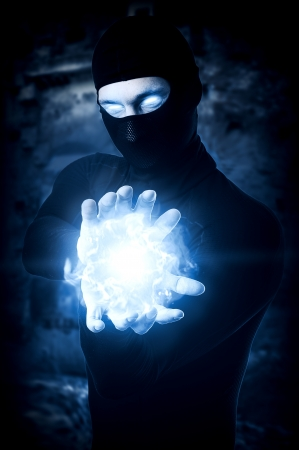 magic eye: Halloween concept. Powerful Male witch or wizard with blue cold fireball in hands. Ball from frozen ice