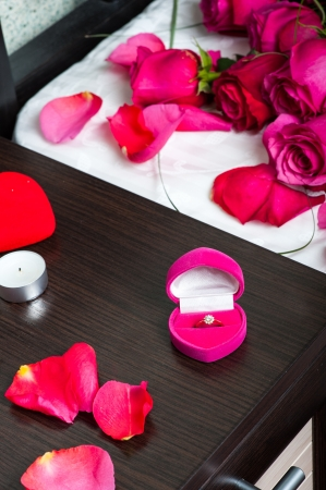 'bedside table': Concept. marriage proposal - roses on a pillow in bed, diamond ring with candles on bedside table