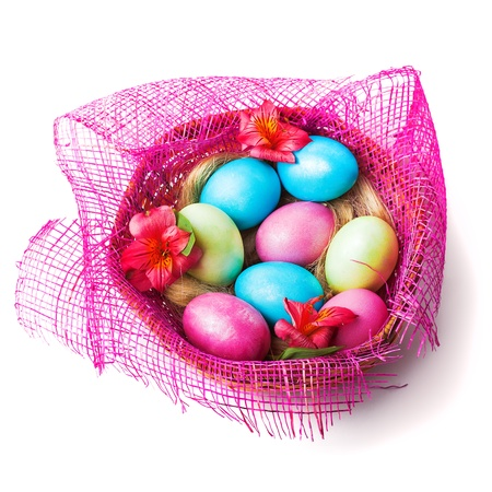 Colorful painted easter eggs in pink basket with flowers photo