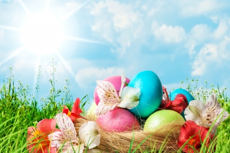 Colorful Easter eggs decorated with flowers in basket in the grass on blue sky background photo