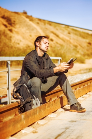 bright picture of travelling young man with backpack. He sitting on railroad and writes on a Tablet PC photo