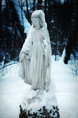 snow-covered Religious sculpture in the courtyard of small town church  photo