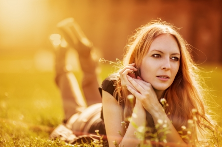 Attractive girl dreaming in a grass with flowers  photo