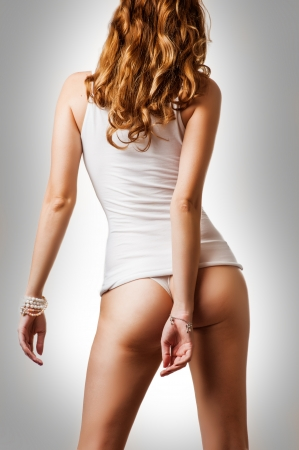 Perfect female body. Woman wearing white cotton undershirt and thong underwear with beautiful buttocks Stock Photo