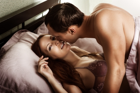 bed sex: Beautiful sexy couple of  lovers  Young man kissing woman in darkness bedroom on bed Stock Photo