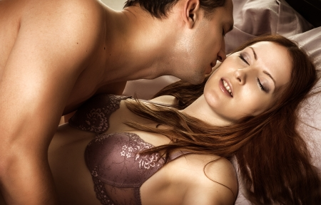 Beautiful sexy couple of  lovers  Young man kissing woman in darkness bedroom on bed Stock Photo