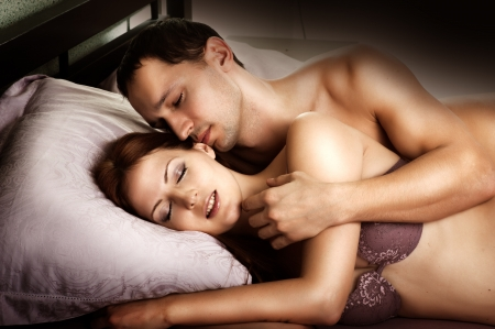 bed sex: Sexy couple of  lovers  Young man kissing woman in darkness bedroom on bed