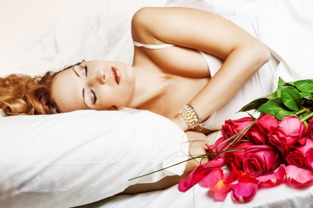 anniversary sexy: Romance  Beautiful slepping woman in white bed with red roses Stock Photo