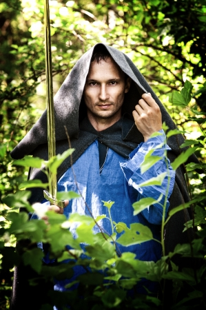 capote: Fantasy foto of handsome mystery man with medieval sword Stock Photo
