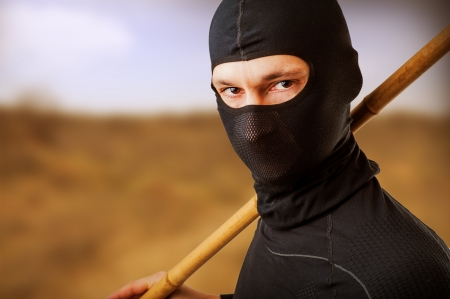 ninja weapons: Close up portrait of male ninja in black mask covered his face Stock Photo