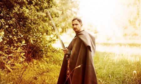 Fantasy portrait of handsome dangerous man with medieval sword photo