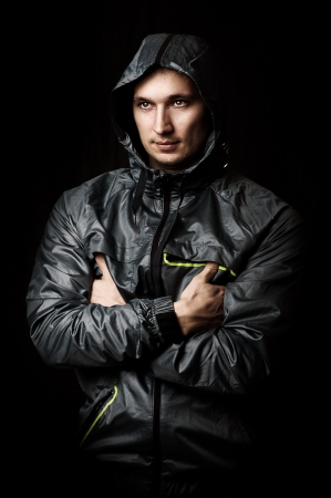 Portrait of young sexy man in sport wear with hood photo