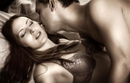 young couple sex: Красивая сексуальная пара влюбленных. Молодой человек, целовать женщину в темноте спальни на кровати Фото со стока