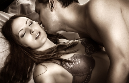 sex bed: Beautiful sexy couple of  lovers. Young man kissing woman in darkness bedroom on bed
