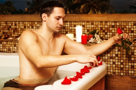 vaporarium: Young man in spa. Romantic jacuzzi with flowers and candles. man decorated bathroom with rose petals waiting for his beloved. Preparing for a date
