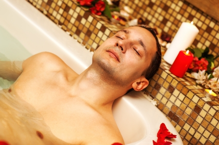 steam bath: Young man in spa. Romantic jacuzzi with flowers and candles Stock Photo