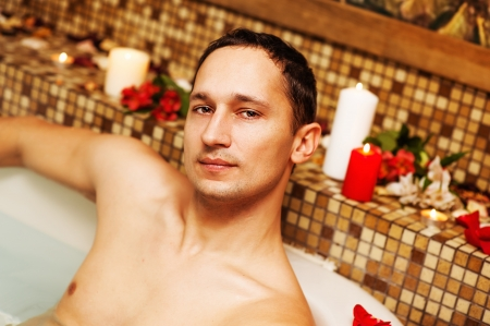 vaporarium: Young man in spa. Romantic jacuzzi with flowers and candles Stock Photo