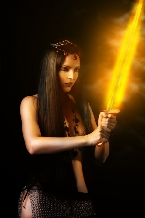 Young sexy woman warrior holding fire sword in hands with long healthy black hair. photo
