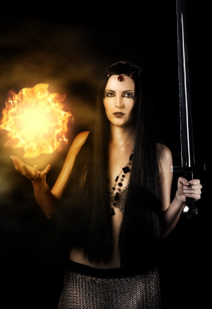 Young sexy woman warrior with long  black hair holding sword and magic fire ball in hands  photo