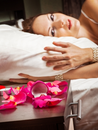 Concept. marriage proposal - beautiful woman on a pillow in bed, diamond ring with candles on bedside table. Focus on ring photo