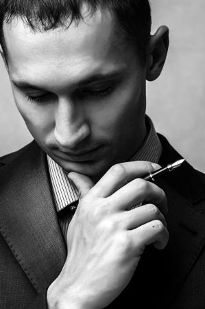 primer plano cara: Pensando exitoso hombre de negocios con la pluma. Cara de cerca