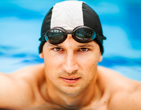 Close up portrait of young handsome swimmer in swimming goggles and hat photo