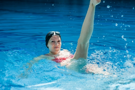 woman trains synchronous swimming at water pool Stock Photo