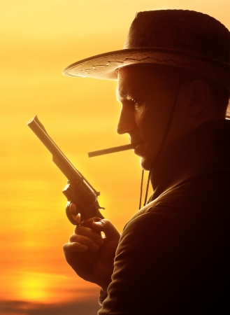 western culture: cowboy in hat with cigar and revolver silhouette