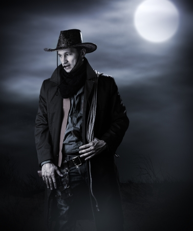 Handsome man in cowboy costume stay in steppe at night with full moon. Vampire Hunter photo