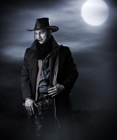vaquero: Hombre guapo en traje vaquero permanecer en la estepa en la noche con luna llena. Vampire Hunter